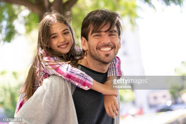 Portrait of sweet daddy carying daughter on back both smiling at camera