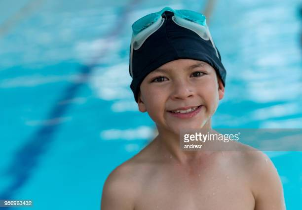 Portrait of sweet little boy looking at camera smiling wearing a swimming cap and googles