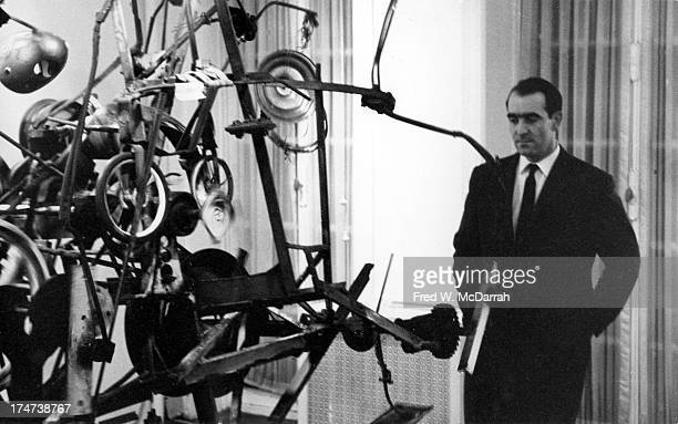 Portrait of Swiss painter and sculptor Jean Tinguely as he poses in front of one of his works at the Alexander Iolas Gallery, New York, New York,...