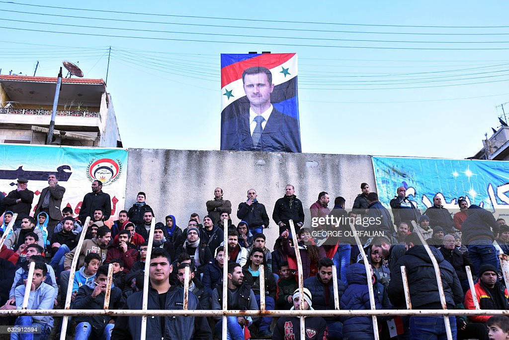 A portrait of Syrian President Bashar al-Assad hangs in the stadium during the Syrian league football match between derby rivals Al-Ittihad and Al-Hurriya, on January 28, 2017, in the northern Syrian city of Aleppo. The Ittihad club beat Hurriya 2-1 in their first match on home turf since rebels took east Aleppo in 2012, dividing the northern city into a regime-held west and rebel-controlled east. / AFP / George OURFALIAN