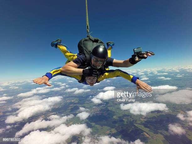 portrait of tandem skydivers free falling above clouds and landscape - truth or dare stock pictures, royalty-free photos & images