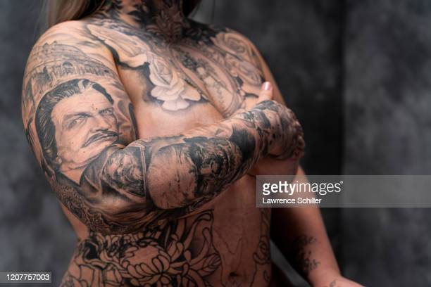 Portrait of tattoo artist Jessa Bigelow as she shows the tattoos on her arm chest and torso New York New York June 21 2019 Her right sleeve features...