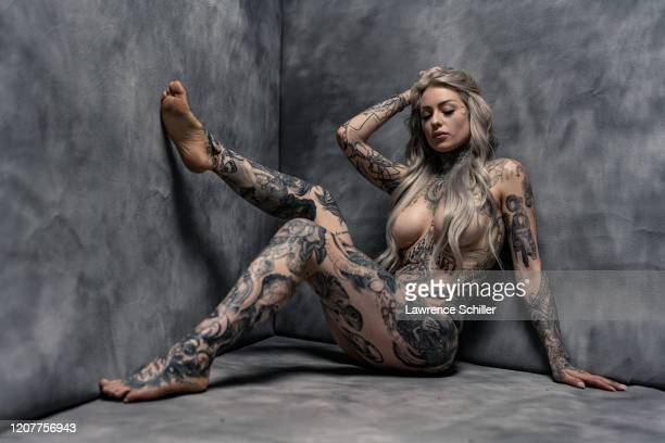 Portrait of tattoo artist Ryan Ashley Malarkey as she shows the tattoos on her arms, chest and torso, and legs, New York, New York, June 25, 2019....