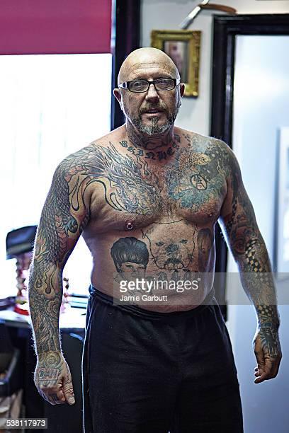 portrait of tattoo enthusiast in studio - brustwarzen piercing stock-fotos und bilder