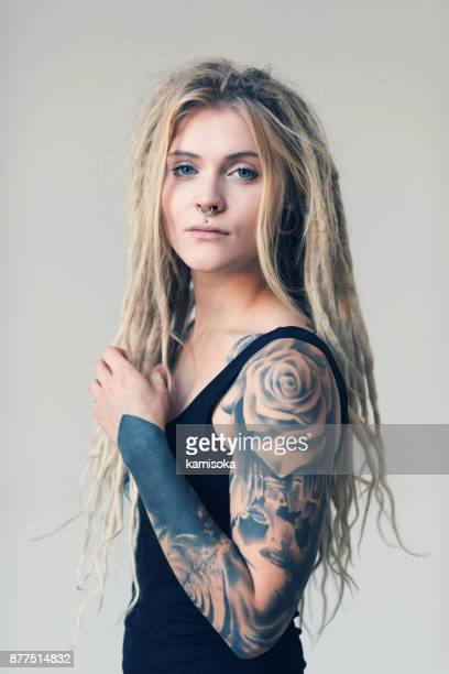 Portrait of tattooed and pierced young women with blond dreadlocks