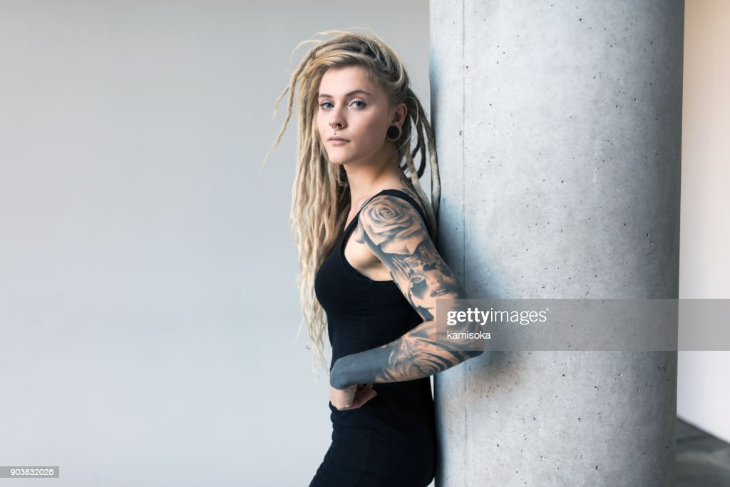 Portrait of tattooed and pierced young women with blond dreadlocks : Stock Photo