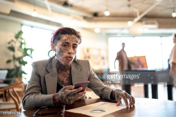 portrait of tattooed businesswoman analyzing graphs with mobile phone at work - accountancy stock pictures, royalty-free photos & images