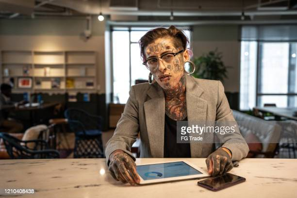 portrait of tattooed businesswoman working with digital tablet at lobby office - bank statement stock pictures, royalty-free photos & images
