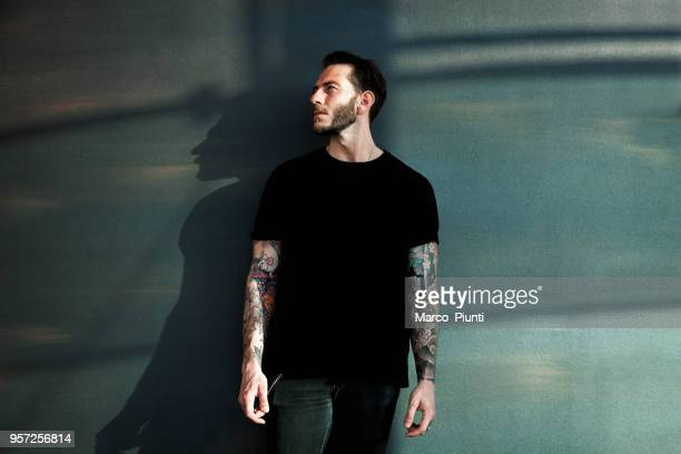 portrait of tattooed young man with black t-shirt - all shirts stock pictures, royalty-free photos & images