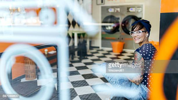 Portrait of tattooed young woman hearing music with earphones in a launderette