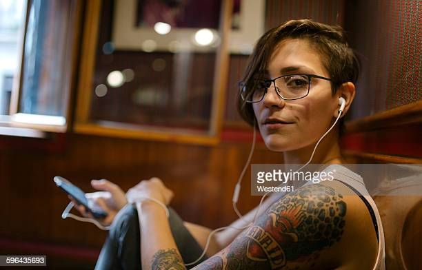 Portrait of tattooed young woman listening music with earphones