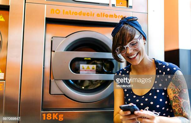 Portrait of tattooed young woman looking at her smartphone in a launderette