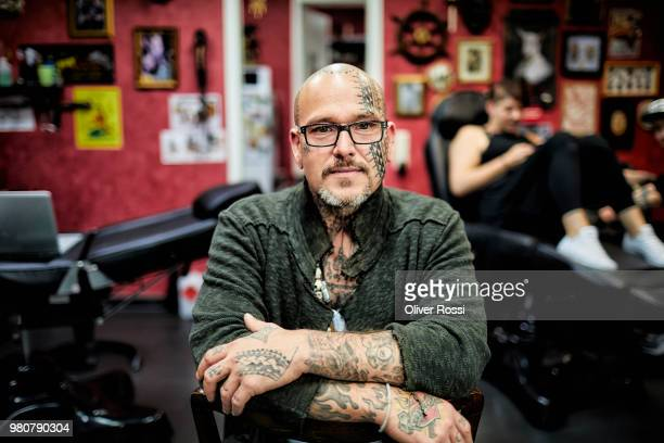 portrait of tattooist sitting in his studio - tätowierung stock-fotos und bilder