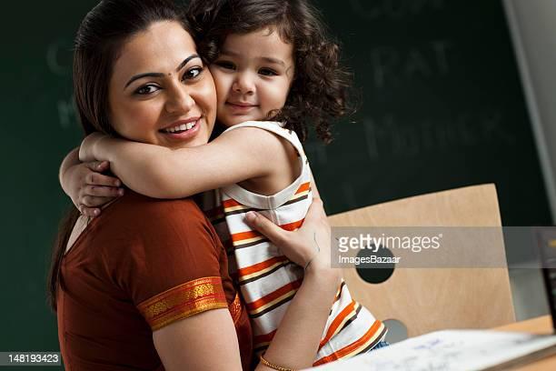 Portrait of teacher and schoolgirl (2-3) embracing