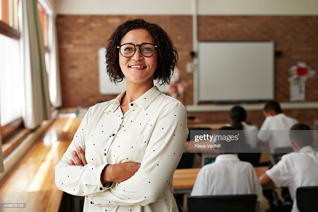 Portrait of teacher in classroom, students in back : Stock Photo