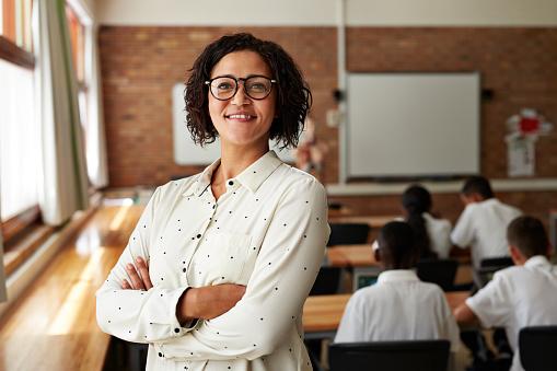 Portrait of teacher in classroom, students in back - gettyimageskorea