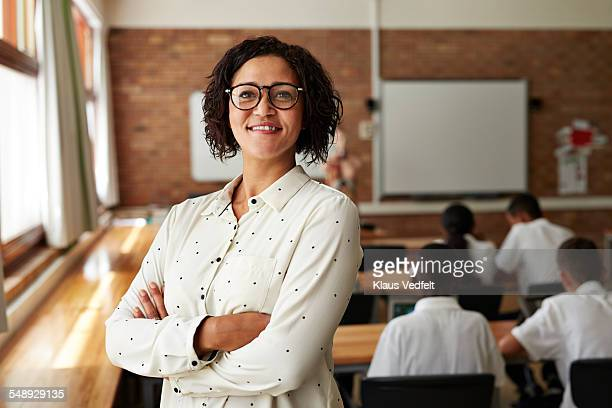 portrait of teacher in classroom, students in back - teacher stock pictures, royalty-free photos & images