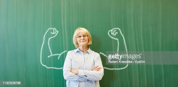 portrait of teacher standing against drawing on blackboard in classroom - blackboard visual aid stock pictures, royalty-free photos & images