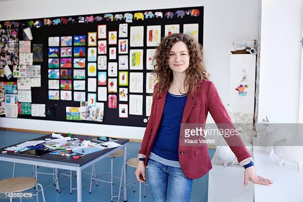portrait of teacher standing in classroom - enseignante photos et images de collection