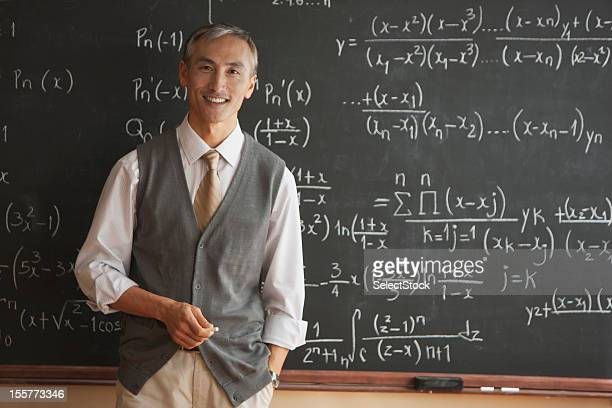 Portrait of teacher with in front of blackboard