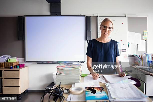 portrait of teacher with papers against blank whiteboard in classroom - sólo con adultos fotografías e imágenes de stock
