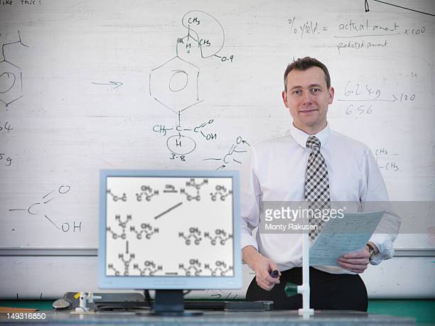 Portrait of teacher with scientific data on board and screen