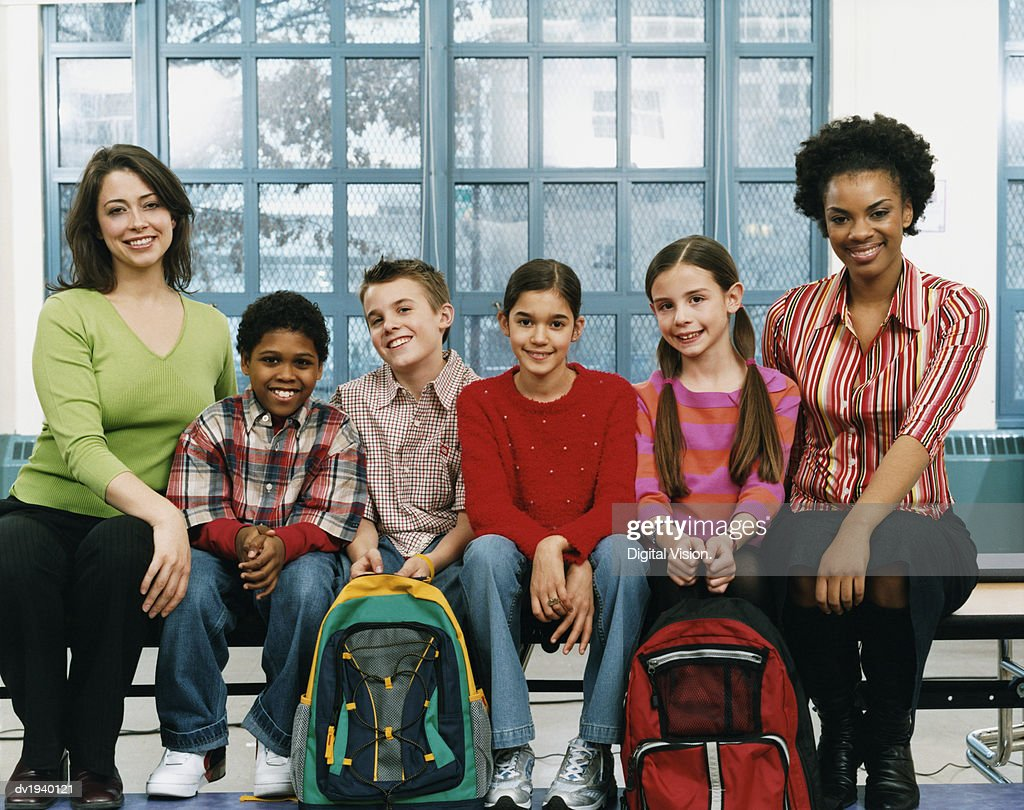 Portrait of Teachers and Primary School Pupils Sitting on a Bench in a School : Stock Photo
