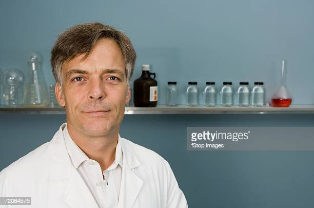 portrait of technician or doctor with specimen bottles in background - 40 44 jaar stock pictures, royalty-free photos & images