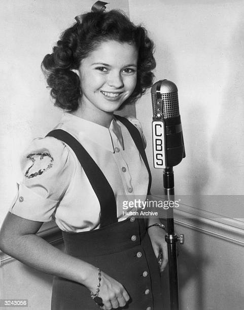Portrait of teenage actor Shirley Temple wearing a blouse and jumper smiling and standing by a CBS radio microphone posing with her thumbs in her...