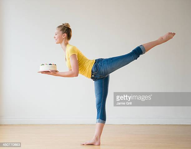 Portrait of teenage (16-17) ballerina holding cake