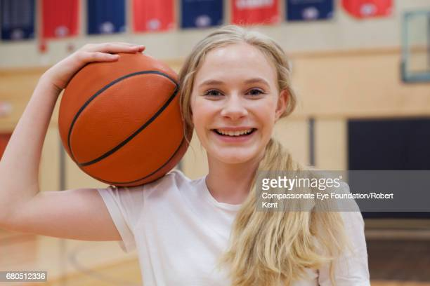 portrait of teenage basketball player in gym - leanincollection stock pictures, royalty-free photos & images