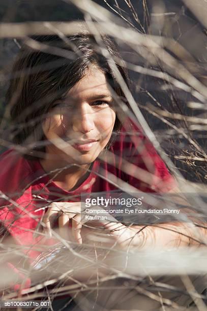 Portrait of teenage boy 916-17) squatting behind twigs