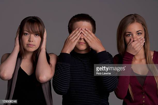 portrait of teenage boy (16-17) and girl (16-17) with young friend, studio shot - see no evil hear no evil speak no evil stock pictures, royalty-free photos & images
