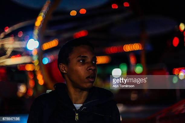 portrait of teenage boy at fairground at night