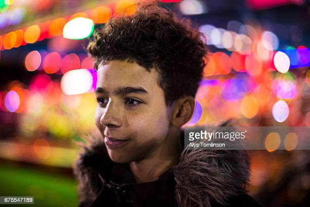 portrait of teenage boy at the fairground at night - focus on foreground stock pictures, royalty-free photos & images