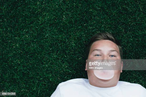 portrait of teenage boy blowing bubble gum bubble - chubby boy stock photos and pictures