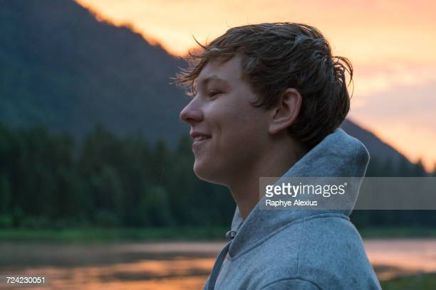 Portrait of teenage boy by river at sunset, Washington, USA