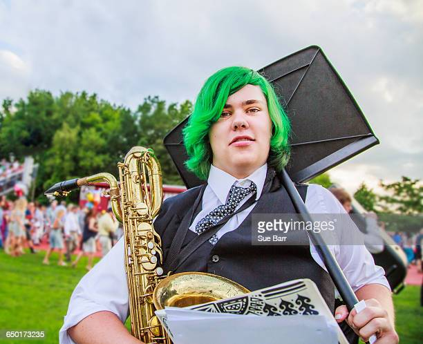 Portrait of teenage boy holding saxophone and music stand
