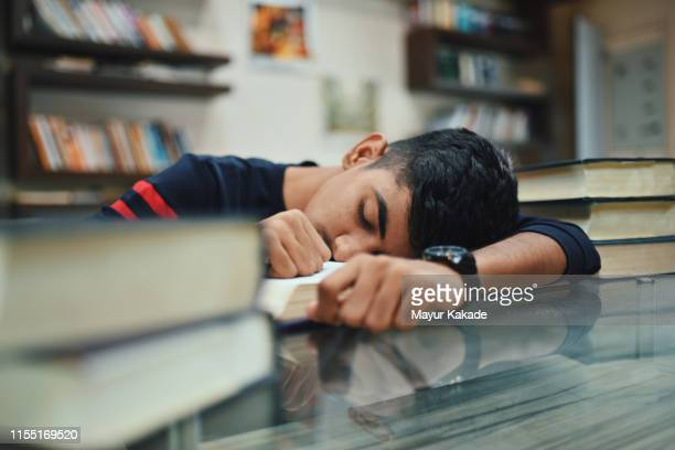 portrait of teenage boy in the library - bad student stock pictures, royalty-free photos & images