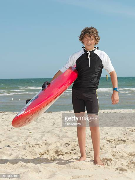 portrait of teenage boy nipper (child surf life savers) carrying surfboard, altona, melbourne, australia - innocence stock pictures, royalty-free photos & images