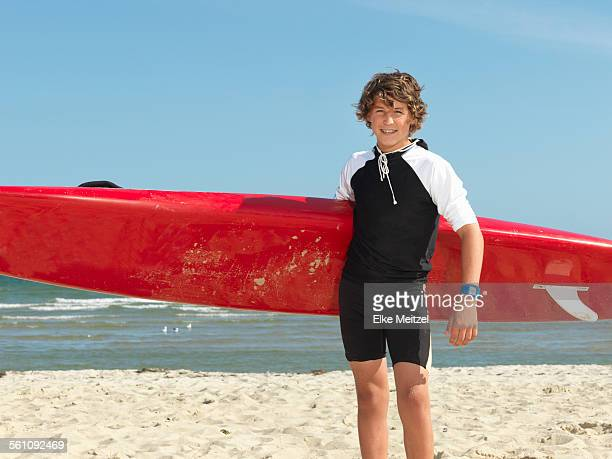 Portrait of teenage boy nipper (child surf life savers) with surfboard, Altona, Melbourne, Australia