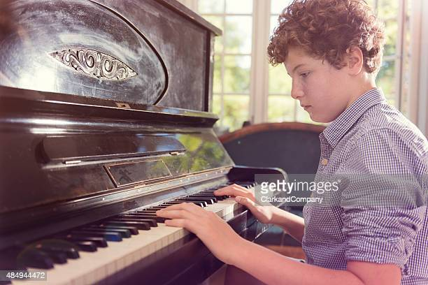 Portrait of Teenage Boy Playing Piano In  Bright Sunlight Room