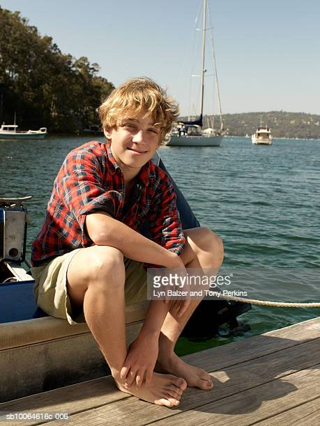 Portrait of teenage boy (13-14) sitting by water, smiling
