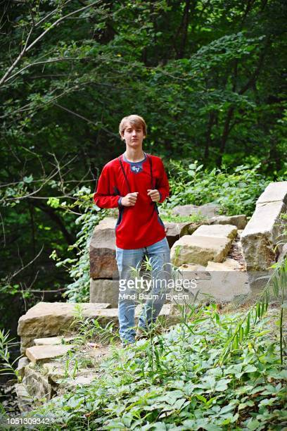 portrait of teenage boy standing in forest - baum stock pictures, royalty-free photos & images