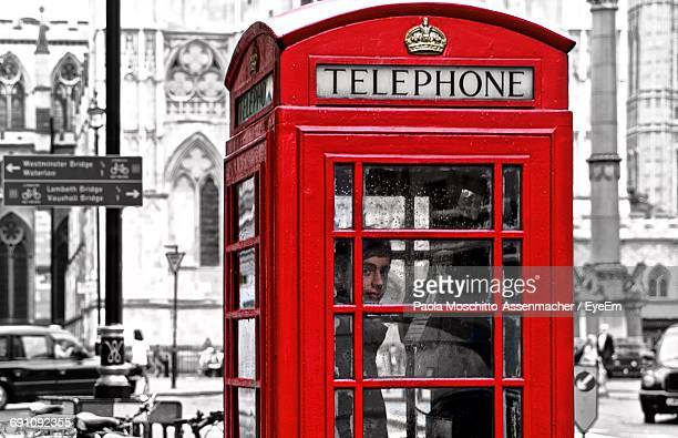 Portrait Of Teenage Boy Standing In Telephone Booth