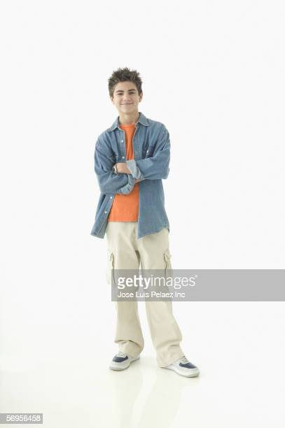 portrait of teenage boy standing with arms crossed - teenage boys stock pictures, royalty-free photos & images