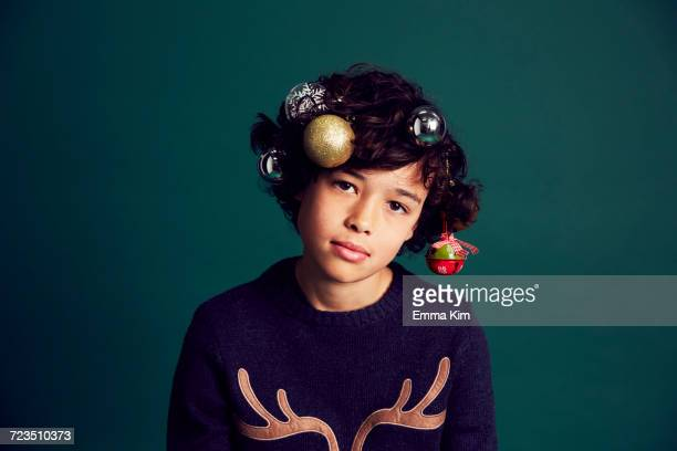 portrait of teenage boy wearing christmas jumper, and baubles in hair - christmas jumper fotografías e imágenes de stock