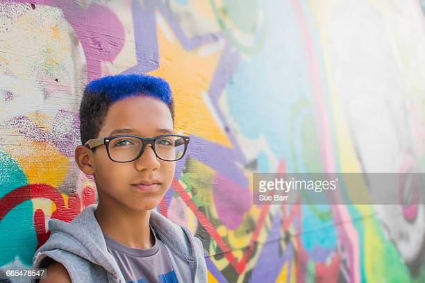 Portrait of teenage boy with blue hair leaning against wall mural at amusement park