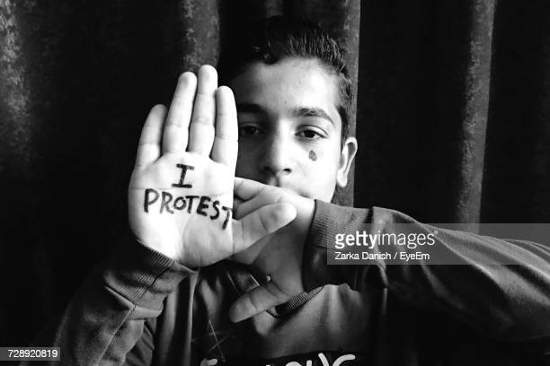 portrait of teenage boy with i protest text on palm against wall - protestor stock pictures, royalty-free photos & images