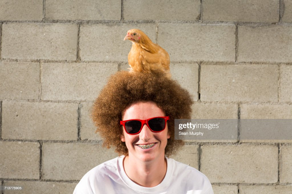 Portrait of teenage boy with red afro hair, chicken sitting on head : Stock Photo